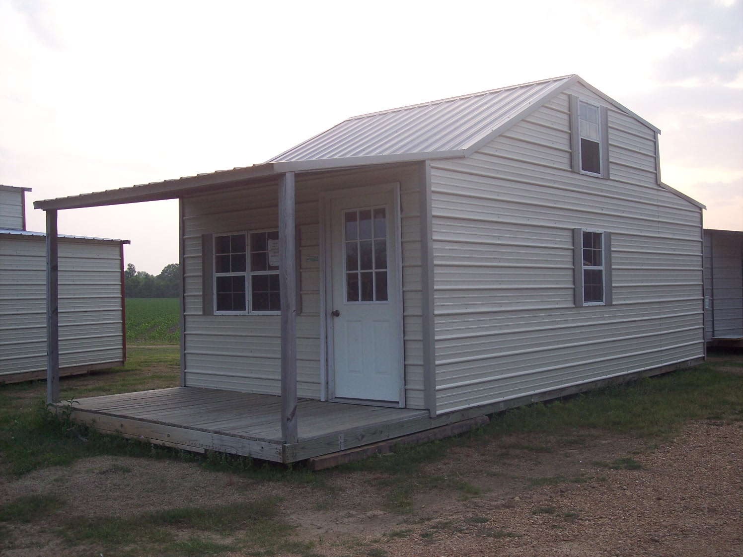 Tan and gray storage building with loft and porch for Shed with porch and loft